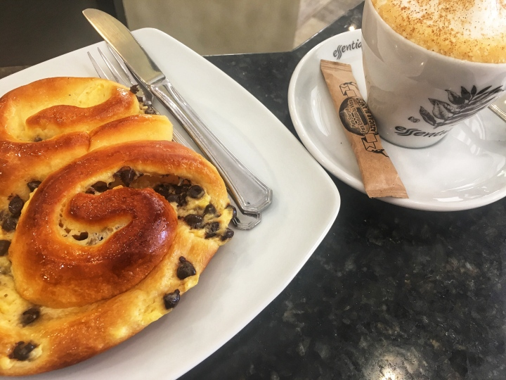 Close-up of braided pastry with chocolate chips and cappuccino