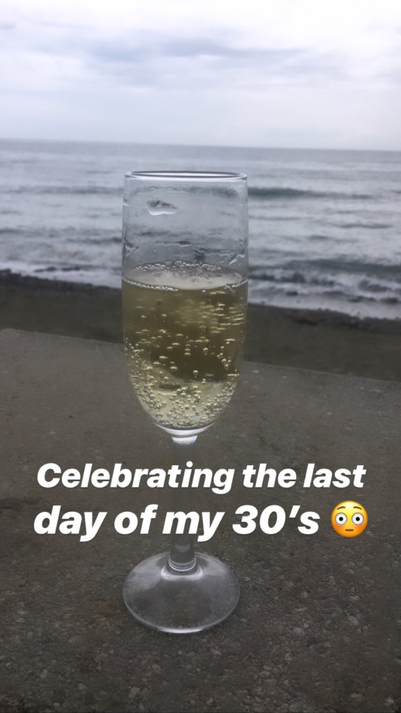glass of cava sitting on concrete ledge with beach and ocean behind it
